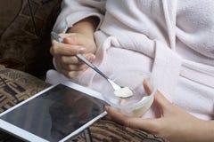 说谎在长沙发的一件家庭浴巾的一个女孩与片剂一起使用 同时他吃酸奶 免版税图库摄影