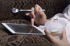 说谎在长沙发的一件家庭浴巾的一个女孩与片剂一起使用 同时他吃酸奶 免版税库存照片