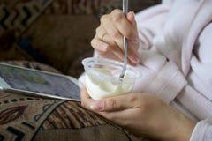 说谎在长沙发的一件家庭浴巾的一个女孩与片剂一起使用 同时他吃酸奶 库存照片
