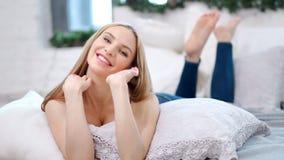 说谎在长沙发的愉快的赤足可爱的妇女舒适白色内部享用的周末 股票视频