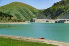 说谎在高山湖Kazenoyam的岸的一条红色小船 好日子在初夏 Botlikh区,达吉斯坦共和国 免版税库存图片