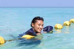 说谎在黄色浮体的全身泳装的妇女 库存图片