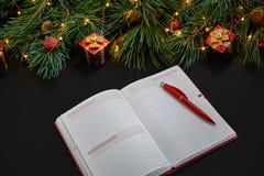 说谎在黑背景顶视图的绿色云杉的分支附近的圣诞节玩具和笔记本 文本的空间 库存图片