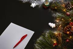 说谎在黑背景顶视图的绿色云杉的分支附近的圣诞节玩具和笔记本 文本的空间 免版税图库摄影