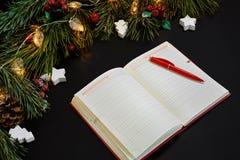 说谎在黑背景顶视图的绿色云杉的分支附近的圣诞节球和笔记本 文本的空间 免版税库存图片