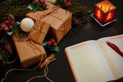 说谎在黑背景顶视图的绿色云杉的分支附近的圣诞节礼物和笔记本 文本的空间 免版税库存图片