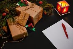 说谎在黑背景顶视图的绿色云杉的分支附近的圣诞节礼物和笔记本 文本的空间 库存图片