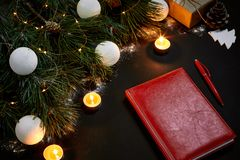 说谎在黑背景顶视图的绿色云杉的分支附近的白色圣诞节球和笔记本 文本的空间 库存照片