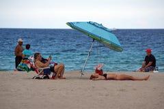 说谎在Dania海滩的一把五颜六色的沙滩伞下的游人 图库摄影