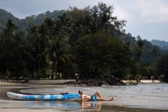 说谎在Ko张,泰国的一条皮船小船附近的愉快的年轻人在2018年4月-幸福的最佳的旅行目的地 免版税库存图片