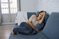说谎年轻可爱的拉丁的妇女长沙发在家让感到遭受的消沉担心哀伤和绝望 免版税库存照片