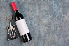 说谎的红酒品尝的酒瓶和拔塞螺旋平的位置有白色空的标签的 免版税图库摄影
