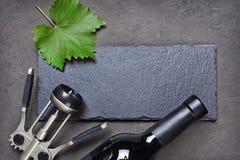 说谎的酒瓶、金属拔塞螺旋和黑板岩板平的位置与葡萄叶子和拷贝空间 库存照片