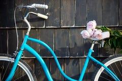 说谎花束桃红色牡丹的特写镜头蓝色葡萄酒自行车 免版税库存图片