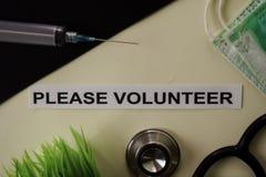请志愿与启发和医疗保健/医疗概念在书桌背景 库存图片