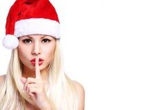 请求圣诞老人妇女 圣诞老人帽子的性感的白肤金发的女孩 免版税库存照片