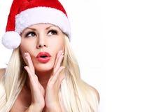请求圣诞老人妇女 圣诞老人帽子的惊奇的美丽的白肤金发的女孩 库存图片
