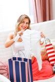 请求怀孕的购物微笑的沙发 免版税库存图片