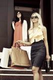 请求查找关于购物的照相机前面微笑新二名视图的妇女 图库摄影