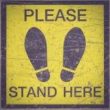 请站立这里脚标志或标志在地板上 免版税库存图片