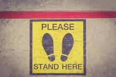 请站立这里脚标志或标志在地板上 免版税库存照片