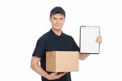 请签字这里得到您的箱子。快乐的年轻送货员hol 库存图片