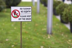 请让开在绿色草坪草的标志在晴朗的夏日弄脏bokeh背景的草 城市生活方式和自然 免版税图库摄影