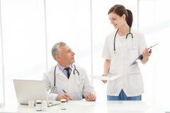 请,签字这里。看彼此的两个医疗同事 免版税库存图片