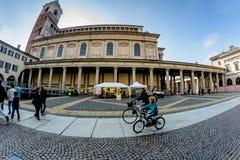 诺瓦腊,意大利- 2016年10月17日:妈妈和儿子在街道在一个古老大厦的背景中骑自行车 库存照片