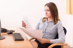 读一个文件的逗人喜爱的妇女在办公室 库存图片