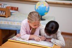 读一个童话的女小学生 免版税库存图片