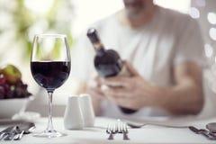 读一个酒瓶标签的人在餐馆 库存图片