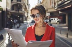 读一些报纸和微笑的时髦的女人 免版税库存照片