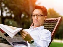 读一张报纸的商人在公园 库存照片