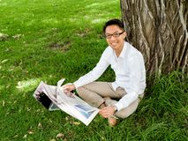 读一张报纸的商人在公园 库存图片