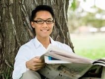 读一张报纸的商人在公园 免版税库存图片