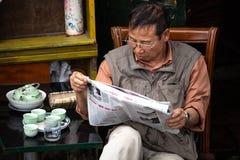 读一张报纸的老人在越南 免版税库存照片