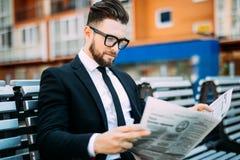 读一张财政报纸的英俊的商人,当坐长凳户外时 库存图片