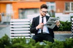 读一张财政报纸的英俊的商人,当坐长凳户外时 免版税图库摄影