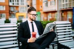 读一张财政报纸的英俊的商人,当坐长凳户外时 免版税库存图片