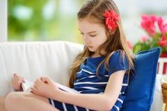 读一本书的可爱的小女孩在白色客厅在美好的夏日 免版税库存照片