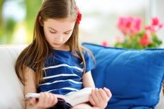 读一本书的可爱的小女孩在白色客厅在美好的夏日 免版税图库摄影