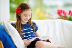 读一本书的可爱的小女孩在白色客厅在美好的夏日 库存照片