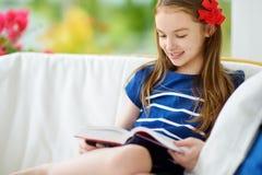 读一本书的可爱的小女孩在白色客厅在美好的夏日 免版税库存图片