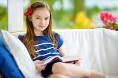 读一本书的可爱的小女孩在白色客厅在美好的夏日 图库摄影