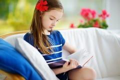 读一本书的可爱的小女孩在白色客厅在美好的夏日 库存图片