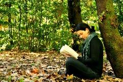 读一本书的女孩在公园 免版税库存照片