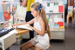 读一本书的小聪明的女孩在学校图书馆里 图库摄影
