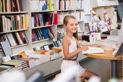 读一本书的小聪明的女孩在学校图书馆里 免版税图库摄影