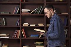 读一本书的年轻人在图书馆里 免版税库存照片